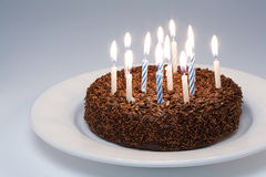 Birthday Cake. Chocolate Birthday Cake with lit candles on a white plate royalty free stock image