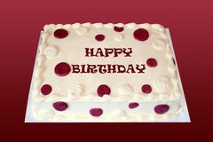 Birthday Cake. A creme colored birthday cake with burgundy spots has happy birthday written on it stock photos