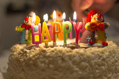 Birthday cake for the baby. On the cake for the baby at the figures of clowns candles Royalty Free Stock Photos