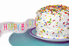 Birthday cake with banner. White birthday cake with sprinkles and party banner Stock Photography