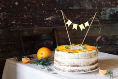 Birthday cake for a birthday in winter with cream and oranges. Birthday cake for a birthday in winter or the New year holiday, with cream and oranges or Stock Photos