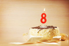 Birthday cake with burning candle as a number eight Royalty Free Stock Photo
