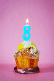 Birthday cake with burning candle as number eight Royalty Free Stock Image