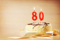 Birthday cake with burning candle as a number eighty. Focus on the candle Stock Images