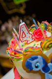 Birthday cake with burning candle as a number four. Royalty Free Stock Photography