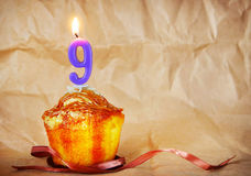 Birthday cake with burning candle as number nine Royalty Free Stock Photo