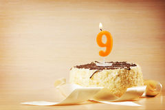 Birthday cake with burning candle as a number nine Stock Images