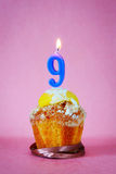Birthday cake with burning candle as number nine Royalty Free Stock Images
