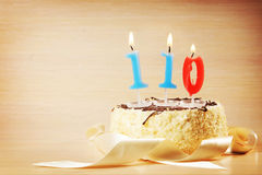 Birthday cake with burning candle as a number one hundred and ten Royalty Free Stock Photos