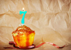 Birthday cake with burning candle as number seven Royalty Free Stock Photography