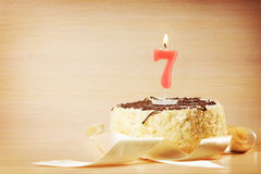 Birthday cake with burning candle as a number seven Royalty Free Stock Photography