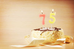 Birthday cake with burning candle as a number seventy five. Focus on the candle Royalty Free Stock Photography