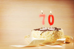 Birthday cake with burning candle as a number seventy. Focus on the candle Stock Image