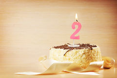 Birthday cake with burning candle as a number two Stock Photos