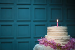 Birthday cake with burning candle on blue background; Stock Photos