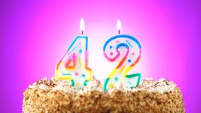 Birthday cake with a burning birthday candle. Number 42. Background changes color