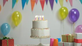Birthday cake with burning candles. Against a wall with decoration flags and balloons stock video