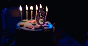 Birthday cake with burning candles and age 6 candle in the dark background with candies in decor royalty free stock image