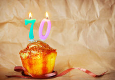 Birthday cake with burning candles as number seventy. On brown paper background Royalty Free Stock Photo