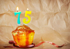 Birthday cake with burning candles as number seventy five. On brown paper background Royalty Free Stock Photo