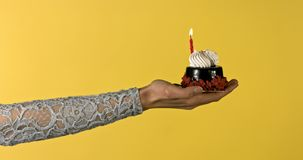 Birthday cake with candle. On woman`s hand. Celebrating birthday concept stock video footage