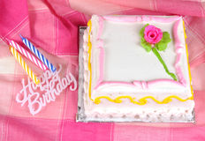 Birthday cake and candles. Colorful birthday cake with candles on pink background Royalty Free Stock Image