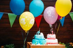 Birthday cake with candles and balloons in background royalty free stock images