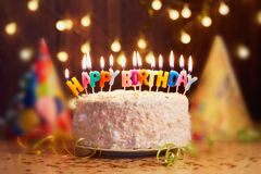 Birthday cake with candles, bright lights bokeh. Royalty Free Stock Images
