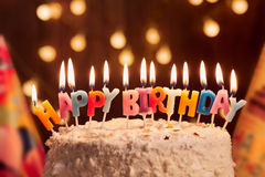 Birthday cake with candles, bright lights bokeh.Celebration. Royalty Free Stock Images