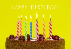 Birthday cake with candles on color background Royalty Free Stock Photos