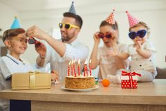 Birthday cake with candles and family out of focus. stock photo