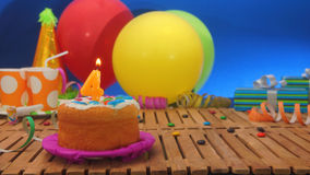 Birthday cake with candles on rustic wooden table with background of colorful balloons Stock Photos