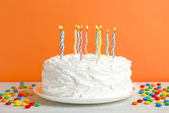 Birthday cake with candles on table against   wall. Birthday cake with candles on table against color wall Royalty Free Stock Images
