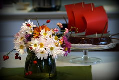 Birthday cake. Birthday chocolate cake with red sails and flowers in foreground Royalty Free Stock Photo