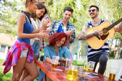 Birthday cake with colorful  candles is gift from friends to you. Birthday cake with colorful candles and guy with guitar are part of girls birthday celebration Royalty Free Stock Images