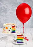 Birthday Cake. Colorful rainbow layered birthday cake decorated with polka dots, sprinkles and buttercream icing. Slice of Cake on separate plate with red royalty free stock image