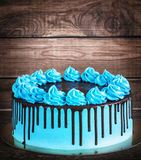 Birthday cake with cream chocolate drips on a dark wooden background.  Stock Image