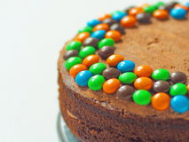 Birthday cake decorated with bright candies upon light background. Selective focus on the left side. Copy space for you text Stock Photos