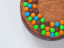 Birthday cake decorated with bright candies upon light background. Top view, selective focus on the top. Copy space for you text Royalty Free Stock Image