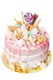 Birthday cake with decorated with candies, lollipop, marshmallows. Pink pastel color. Balloons on background. Isolated