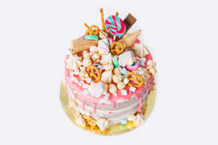Birthday cake with decorated with candies, lollipop, marshmallows. Pink pastel color. Balloons on background. Isolated Stock Photo