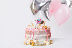Birthday cake with decorated with candies, lollipop, marshmallows. Pink pastel color. Balloons on background Stock Image
