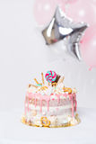Birthday cake with decorated with candies, lollipop, marshmallows. Pink pastel color. Balloons on background Stock Photography