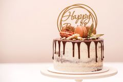 Birthday cake decorated with golden macaroons and chocolate pieces. Elegant naked cake topped by chocolate. Birthday party