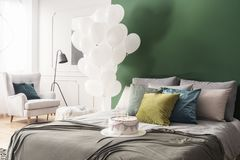 Birthday cake on bed with grey duvet and colorful pillows in bright interior with bunch of white balloons and copy space on. Birthday cake on double bed with stock photo