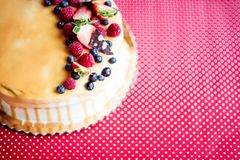 A birthday cake on a glass stand on the table, fruit on top. Top view. Royalty Free Stock Image