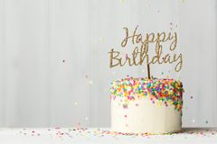 Birthday cake with gold banner. Colorful birthday cake with golden happy birthday banner and falling sprinkles Stock Image