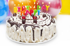 Birthday cake. Happy Birthday cake with burning letter candles and party balloons in background Stock Photos