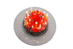 Birthday cake with lighted candles on plate Stock Photos