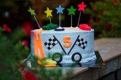 Birthday cake with mastic stars and cars figures for boy.